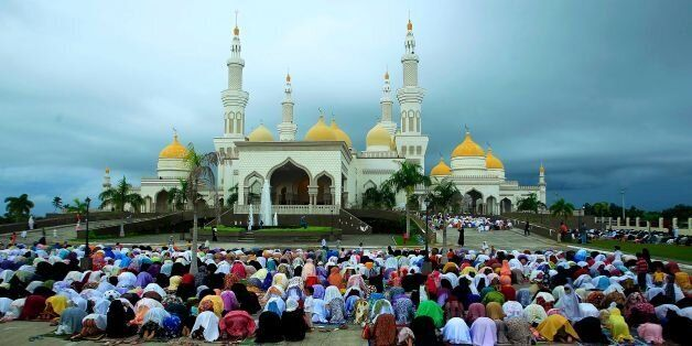 CORRECTION - Filipino Muslims participate in morning prayers as they celebrate Eid al-Fitr at the Sultan...