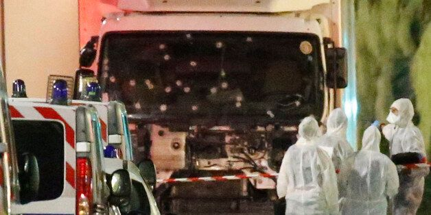 French police forces and forensic officers stand next to a truck July 15, 2016 that ran into a crowd...