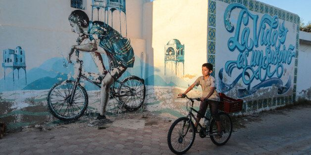 A Tunisian boy cycles past street art in Erriadh, a village on the resort island of Djerba, south of...