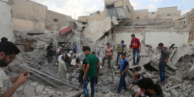 Men look for survivors under the rubble of a damaged building after an airstrike on Aleppo's rebel held...