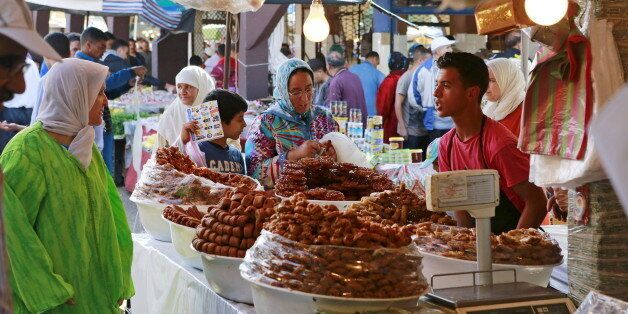 A vendor sells traditional cakes of fried honey and flour pastries to customers during the first day...