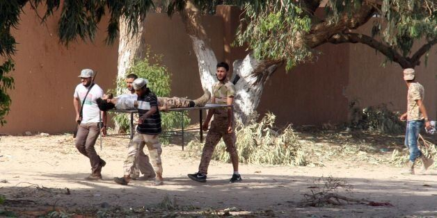 Forces loyal to Libya's UN-backed unity government carry a comrade wounded during clashes with jihadists...