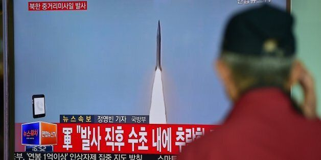A man watches a TV news showing file footage of a North Korean missile launch at a railway station in...