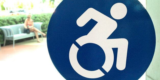 In this Wednesday, Oct. 7, 2015 photo, a modernized handicapped sign is affixed to a door at the The...