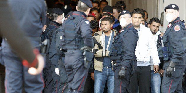 Policemen guard as Tunisian would-be immigrants disembark from a ferry boat during their evacuation from...