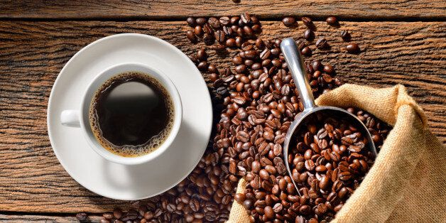 Cup of coffee and coffee beans on wooden