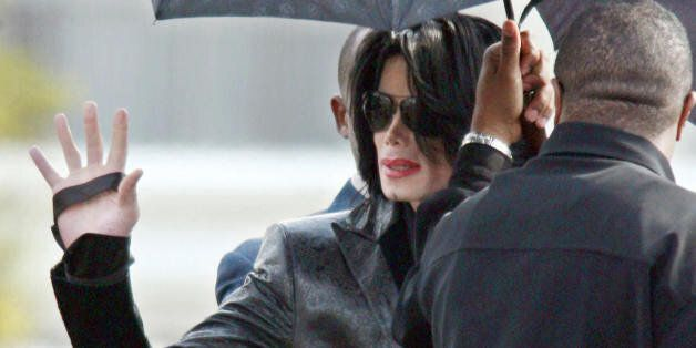 Tokyo, JAPAN: US pop star Michael Jackson waves to Japanese fans as he walks to a helicopter at a heliport...