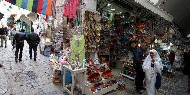 Tunisians walk near at a souvenir shop in the medina, the old city of Tunis, Tunisia, February 16, 2016....
