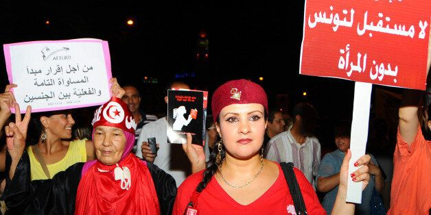 In this Monday, Aug. 13, 2012 photo Tunisian women carry placards protesting their rights which