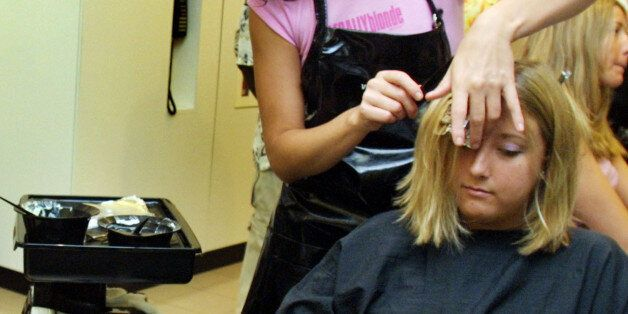 391650 02: Lorraine Connelly checks her hair in a mirror as Laura Walz gets a hair color treatment by...
