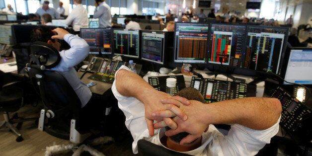 A trader from BGC, a global brokerage company in London's Canary Wharf financial centre reacts during...