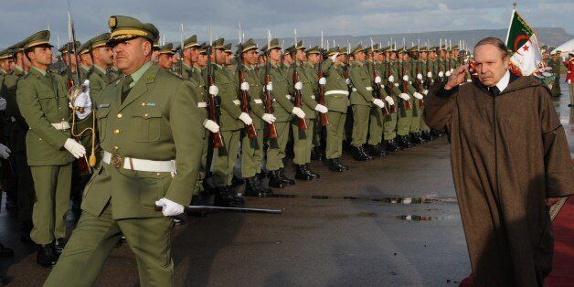 President Abdelaziz Bouteflika reviews an honor guard upon his arrival at Oran airport on December 16,