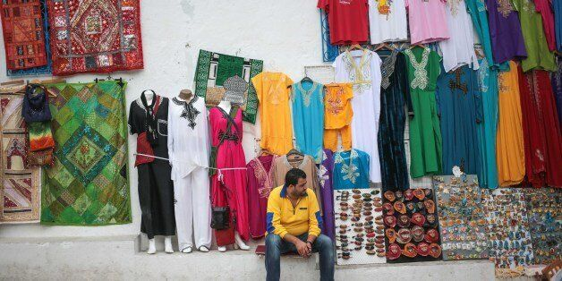 A shop owner waits for tourists outside his shop at the touristic village of Sidi Bou Said, some 20 kilometers...