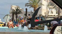 Des Tunisiens se baignent dans une fontaine publique pour échapper à la chaleur