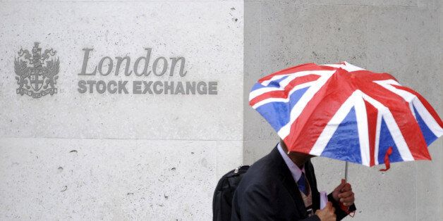 A worker shelters from the rain as he passes the London Stock Exchange in the City of London at lunchtime...