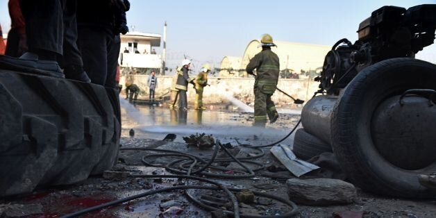 TOPSHOT - Afghan firefighters wash a road at the site of a suicide car bomb near the international airport...