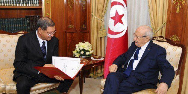New Tunisian Prime Minister Habib Essid, left, and Tunisian President Beji Caid Essebsi check the list...
