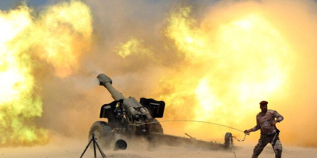 A member of the Iraqi security forces fires artillery during clashes with Islamic State militants near...