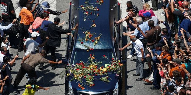 Well-wishers touch the hearse carrying the body of the late boxing champion Muhammad Ali during his funeral...