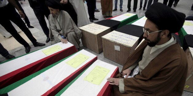 Clerics pray next to coffins of victims of Friday's bombing at the Imam Sadeq mosque in Kuwait City,...