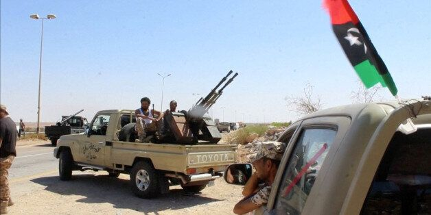 Forces aligned with Libya's new unity government are seen on the road as they advance on the eastern...