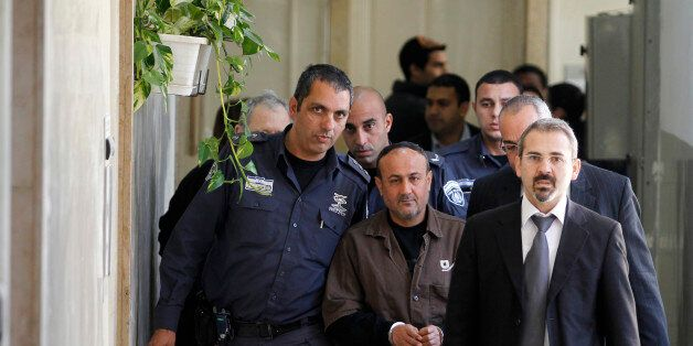 An Israeli prison guard (L) escorts jailed Fatah leader Marwan Barghouti (C) to a deliberation at Jerusalem...