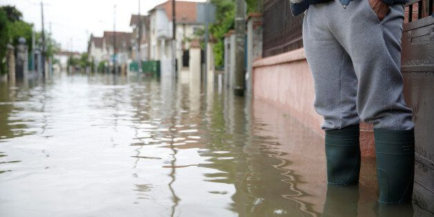 A resident stands in front of his house in a flooded suburb of Villeneuve Saint-Georges, outside Paris,...