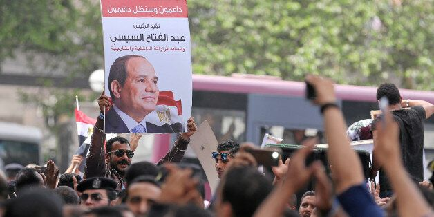 Pro-government protesters hold poster of Egyptian President Abdel Fattah al-Sisi and shout slogans against...