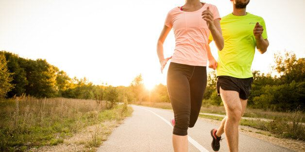 Detail of young people jogging together in nature with sun setting behind