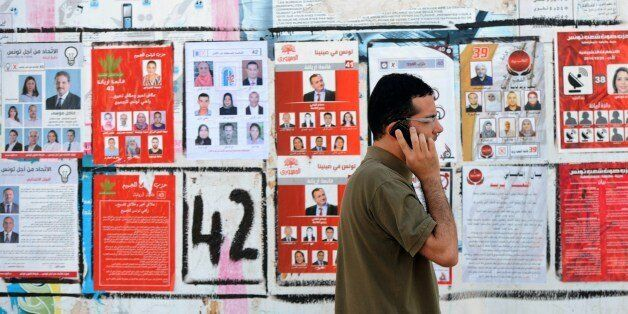 A Tunisian speaks on the phone as he walks past election posters put up on a street ahead of the parliamentary...