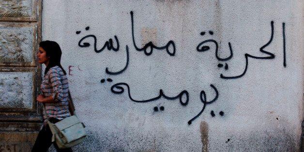 A Tunisian woman walks past a graffiti which