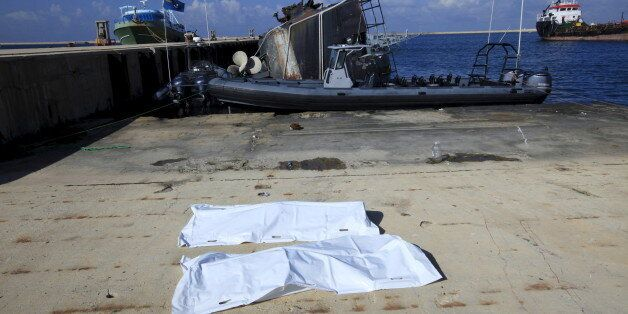 Bags containing a body of two migrants, who died after a boat sank off the coast, lay in a navy base...