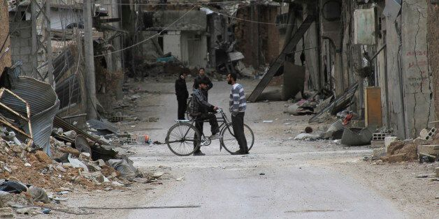 Men chat near buildings damaged by what activists said was shelling by forces loyal to Syria's President...