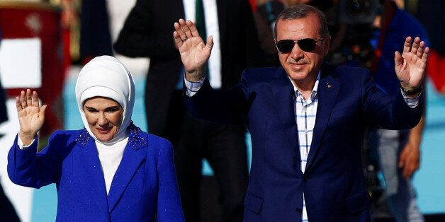Turkish President Tayyip Erdogan, accompanied by his wife Emine Erdogan, greets supporters during a rally...