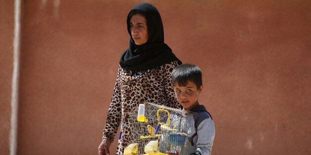 A woman and a boy that fled Manbij city carry a bird cage after arriving in the areas that Syria Democratic...