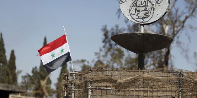 A Syrian national flag flutters next to the Islamic State's slogan at a roundabout where executions were...