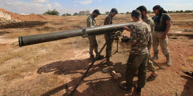 Rebel fighters from the First Regiment, part of the Free Syrian Army, prepare to fire a Grad rocket from...