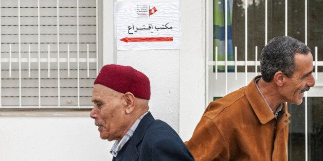 Tunisians walk past a polling station in Tunis, Tunisia, Sunday Dec. 21 , 2014. Tunisians voted on Sunday...