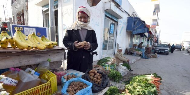 Tunisian vendor Amara Labiadh, 60, poses as he sells white truffles at a market on February 6, 2016 in...