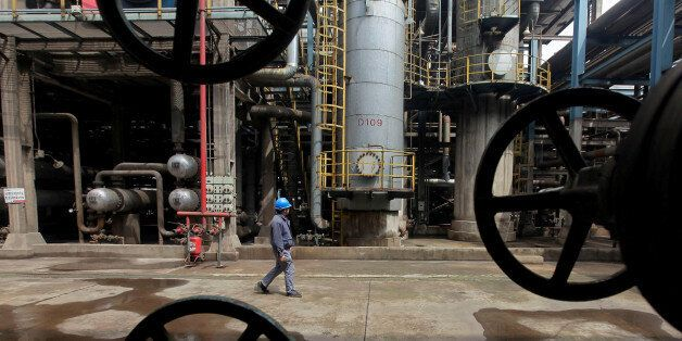 A worker walks past oil pipes at a refinery in Wuhan, Hubei province March 23, 2012. REUTERS/Stringer/File