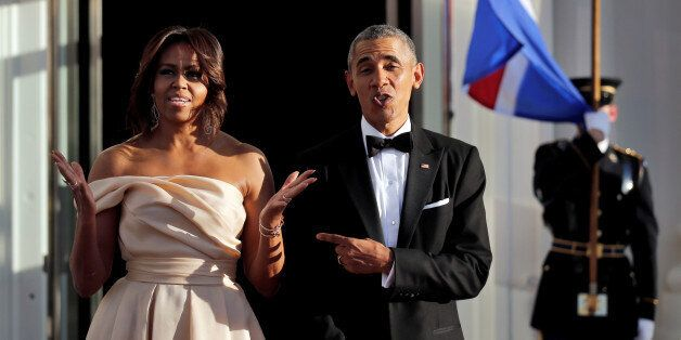 U.S. President Barack Obama and First Lady Michelle Obama react while waiting for the arrival of the...