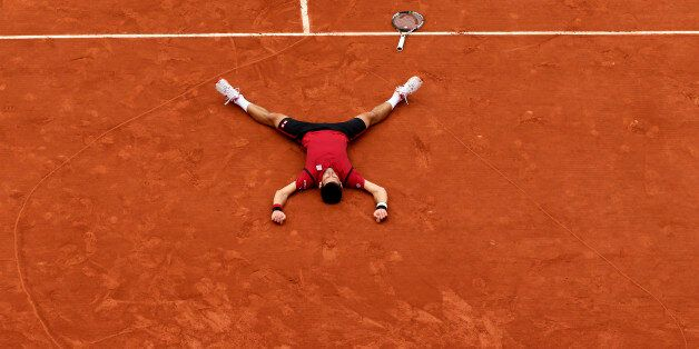 Serbia's Novak Djokovic lays on the clay in a heart in drew after defeating Britain's Andy Murray during...