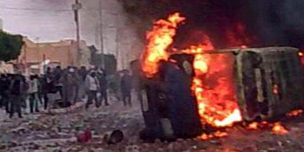 In this frame grab image taken from amateur video and acquired by APTN protesters are seen amid a burning...