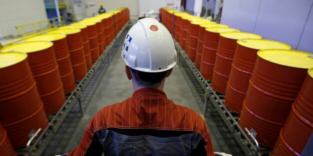 An employee stands in front of lines of oil barrels at Royal Dutch Shell Plc's lubricants blending plant...