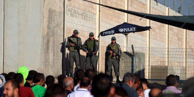 Israeli border police officers stand guard as Palestinians wait to cross through the Qalandia checkpoint...