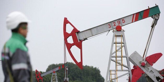 A worker looks at a pump jack at an oil field Buzovyazovskoye owned by Bashneft company north from Ufa,...