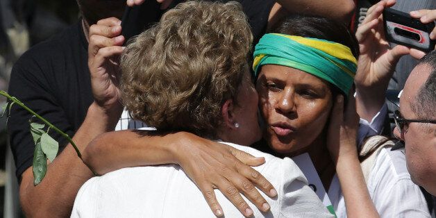 A supporter hugs Brazilian President Dilma Rousseff as she leaves Planalto presidential palace in Brasilia,...