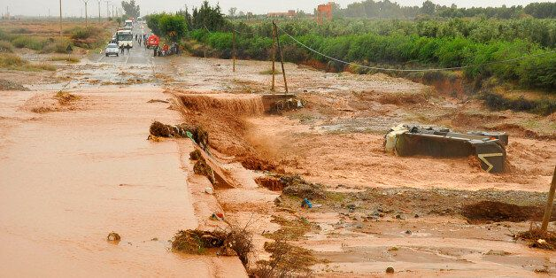 People look at a road submerged in floodwaters near southern Marrakech, October 31, 2012. Torrential...