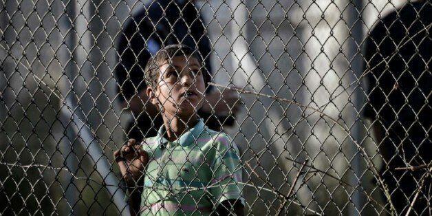 Un enfant regarde à travers les grillages du centre de détention de migrants de Moria à Mytilène en Grèce...