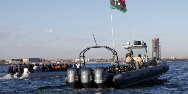 Libyan coast guards (R) escort migrants, who tried to flee to Europe, after the migrants were stopped...